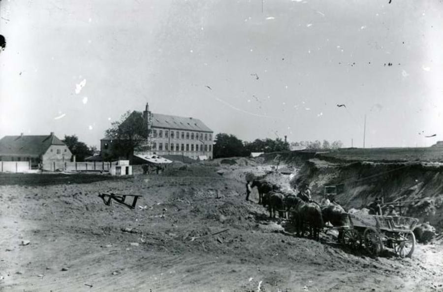 Billededet viser  Aarhus Oliefabriks lagerbygning Sukkerhuset på det senere hjørne af H. N. Clausensgade og Brammersgade. I baggrunden ses Aarhus Kalkværk og Wallensteins skanse. Ca. 1884.