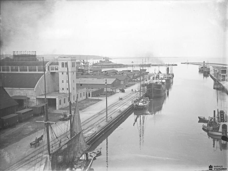 Billedet viser kajanlægget ved den nye oliefabrik på Sydhavnen. Billedet er taget ved Slippen. Til højre ses Aarhus Oliefabriks tårn. Ved siden af ses DSB's kuloplag på Søndre Mole (senere Mellemarmen). Ebbesen Foto, Ca. 1923