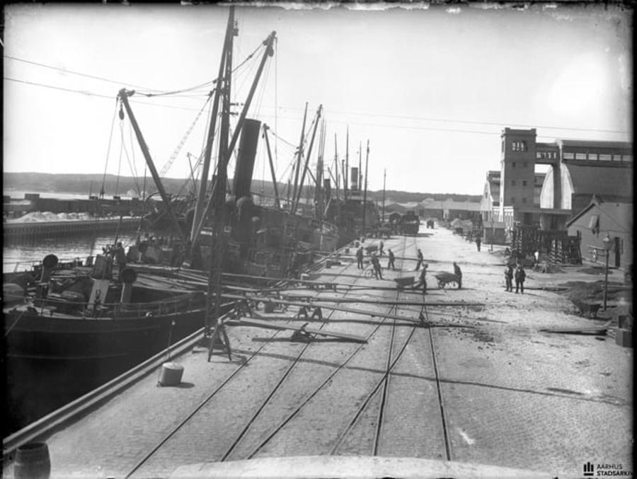 Billedet viser arbejde på kajen ud for Aarhus Oliefabriks havneanlæg. Fragtskibe bliver lastet med kopra. Set mod syd. Formodentlig fotograferet fra taget af en jernbanegodsvogn