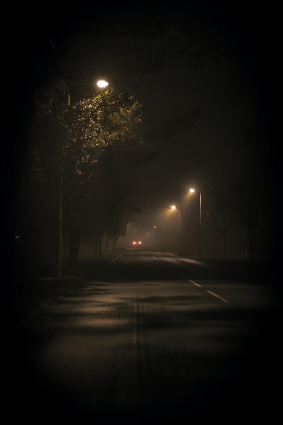 Mørk gade med enkelte gadelamper