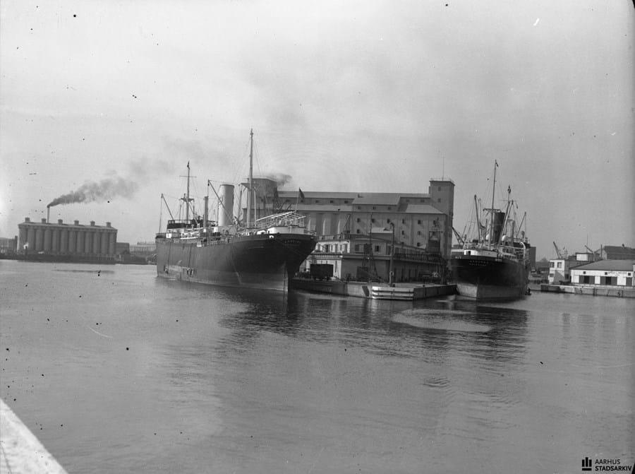 Billedet viser fragtskibe ved Kornpieren. Skibsmalere på arbejde ved dem begge. I billedets venstre side ses Aarhus Oliefabriks siloanlæg ved kaj 109. Foto: Aage Fredslund Andersen
