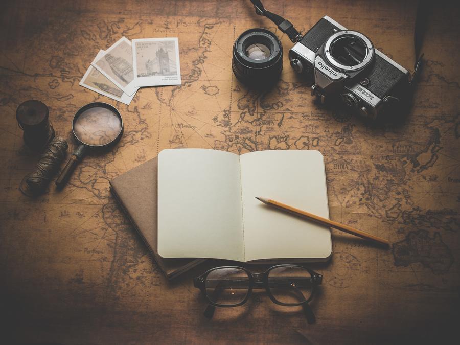 Foto af flade med landkort, notesbog, briller, forstørrelsesglas, fotografiapparat og fotografier