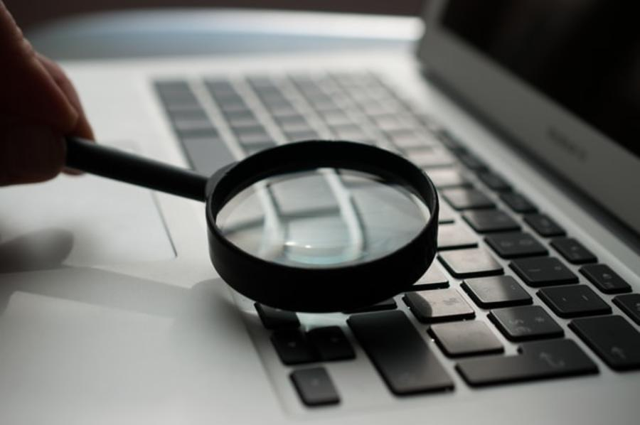PC med forstørrelsesglas liggende på tastaturet