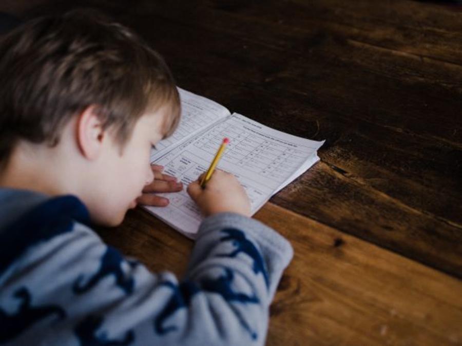 Dreng laver opgaver ved et spisebord