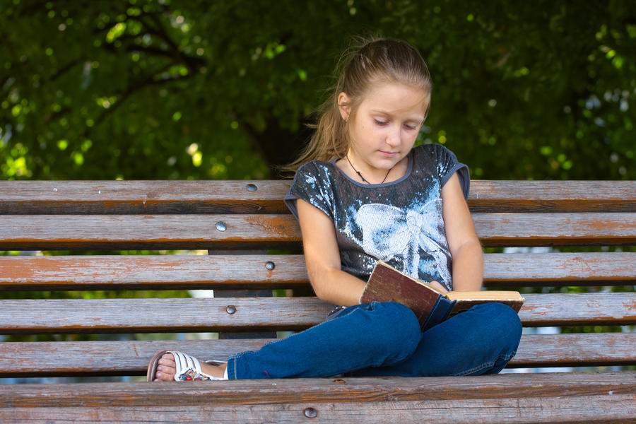 En pige sidder på en bænk og læser