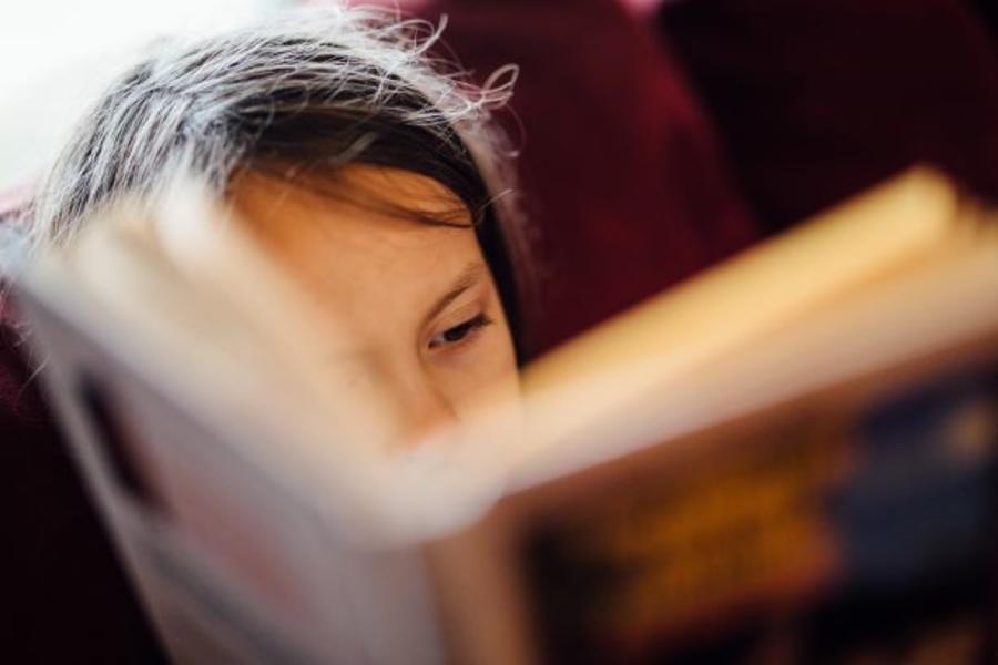 Barn der læser i en bog
