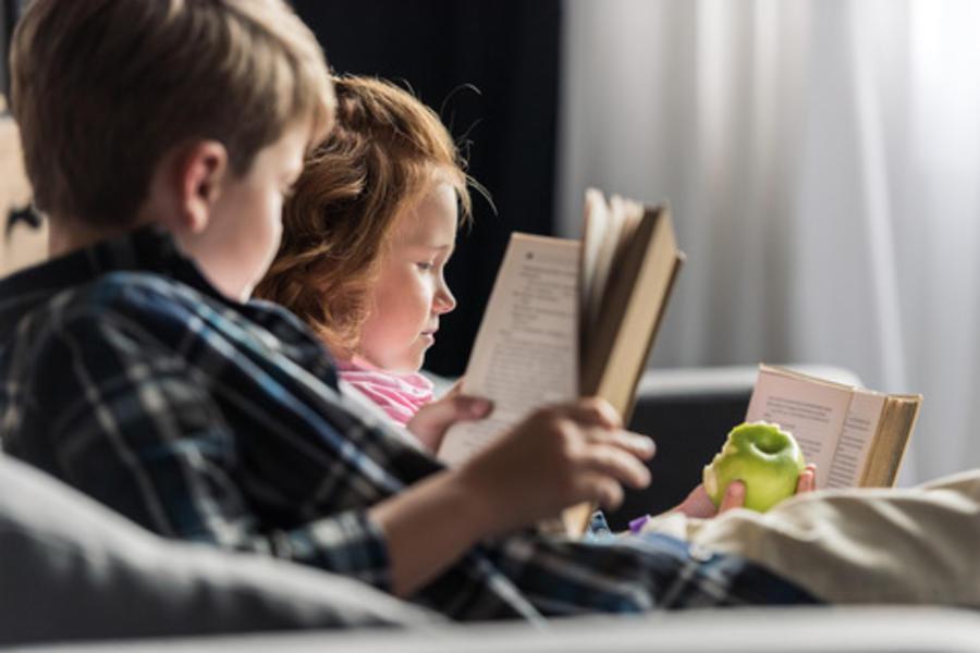 Børn læser i en sofa