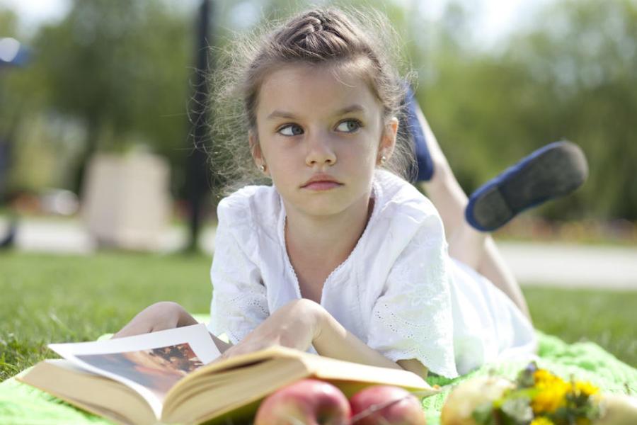 Pige ligger og læser i græsset