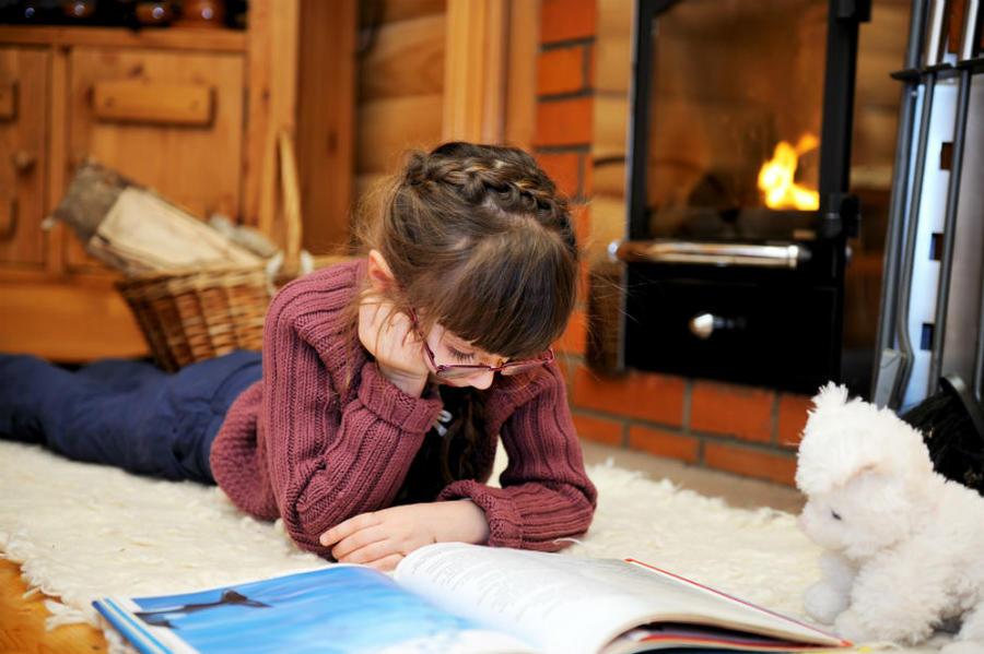 Pige der ligger på gulvet og læser i en bog
