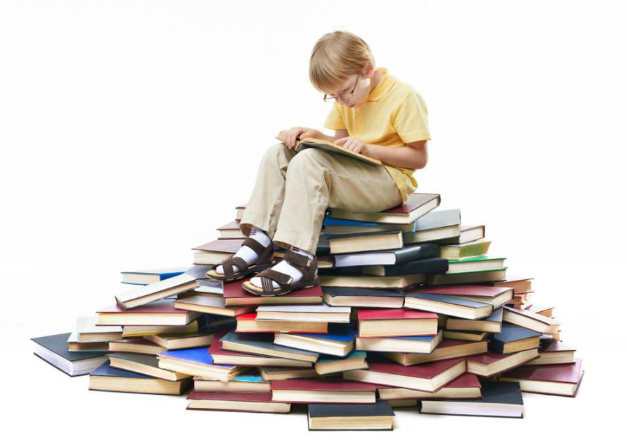 En dreng på en stak bøger