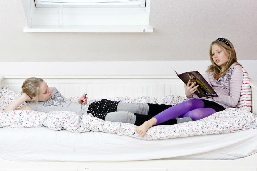 Piger sidder og læser i en seng