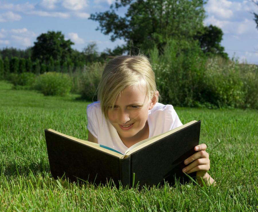 En pige ligger i græsset og læser en bog