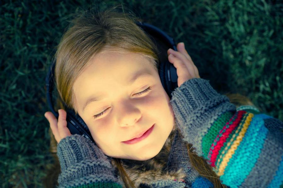 Pige lytter til lydbog med lukkede øjne