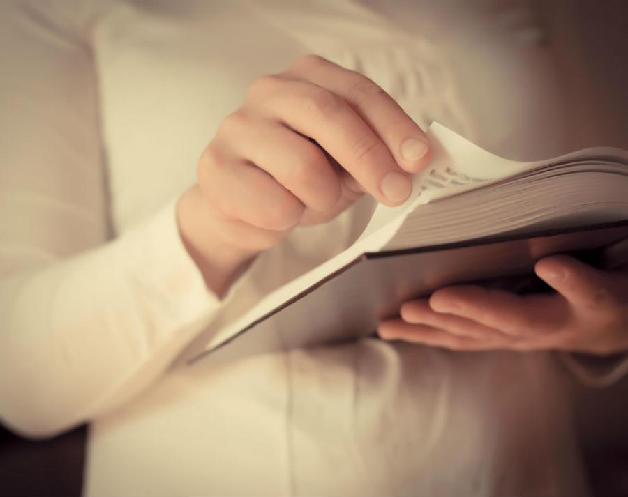 Mand der bladrer i en bog