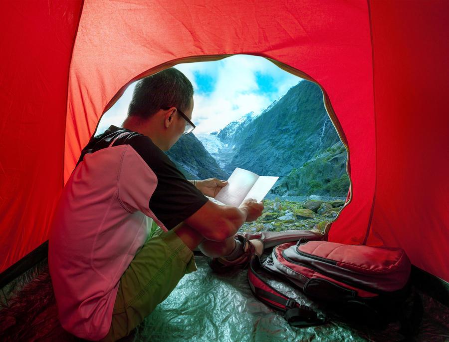 Billede af en mand i et telt, der læser i en bog