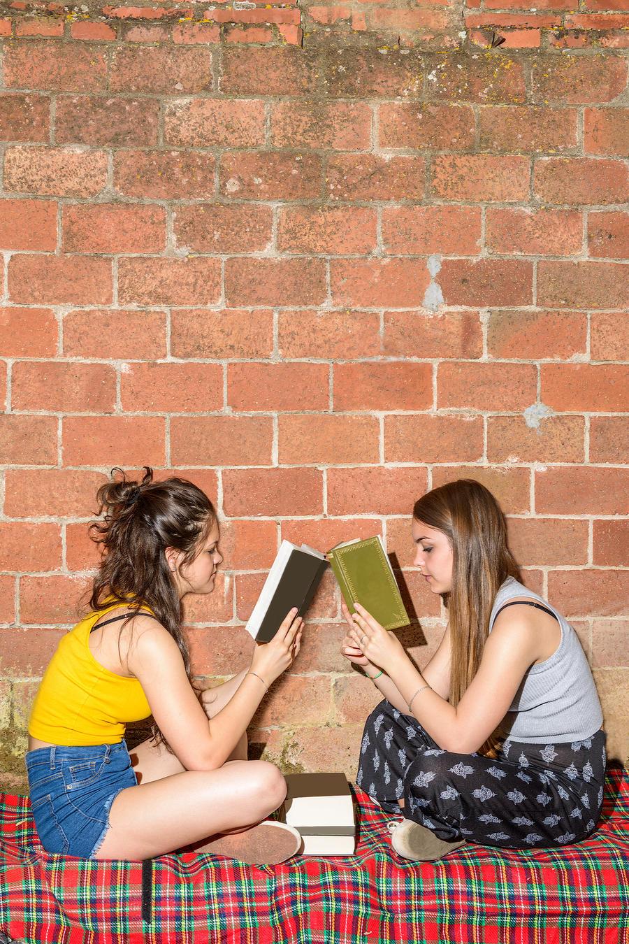 To teenage piger sidder på jorden med ansigterne vendt mod hinanden og læser i hver deres bog.