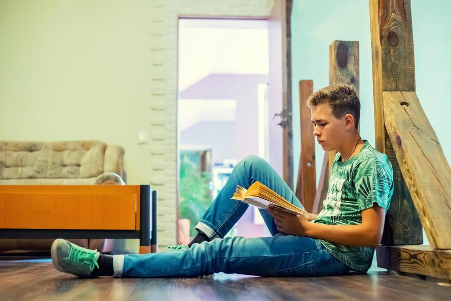 Teenage dreng sidderpå trægulv og læser i en bog.