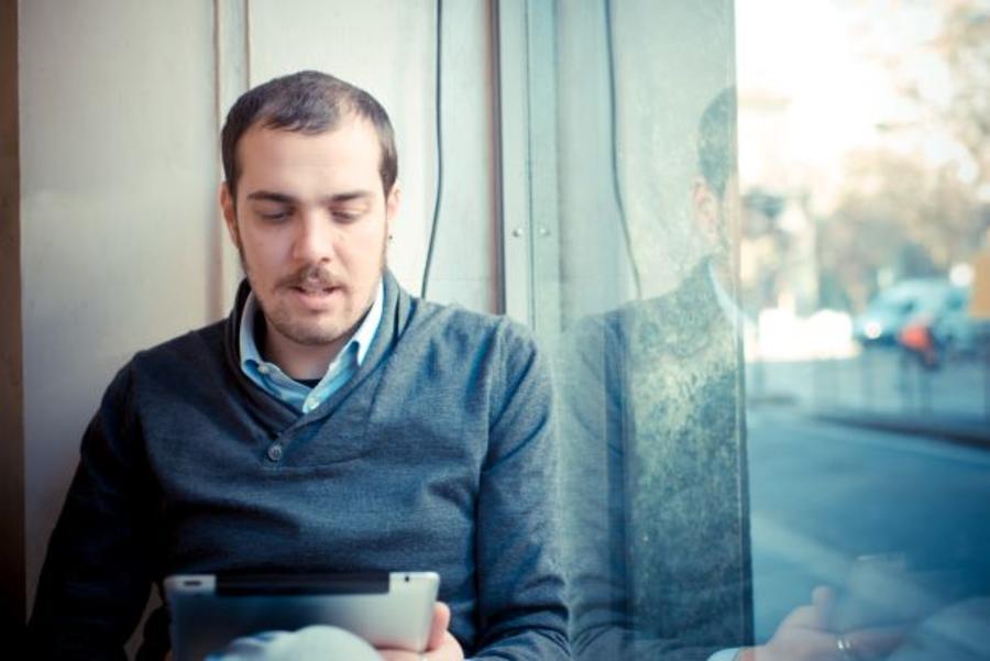 Mand læser en ebog på en tablet