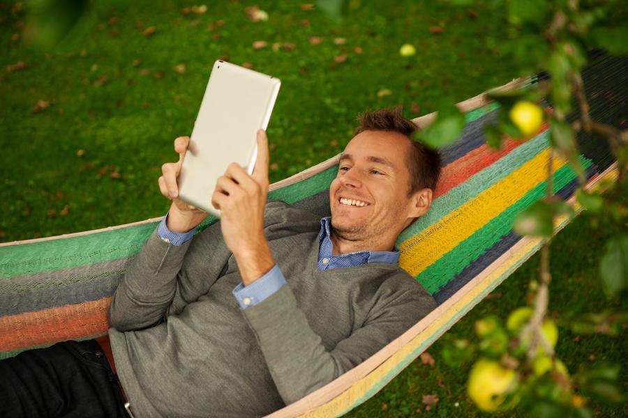 Mand ligger i hængekøje og læser en ebog