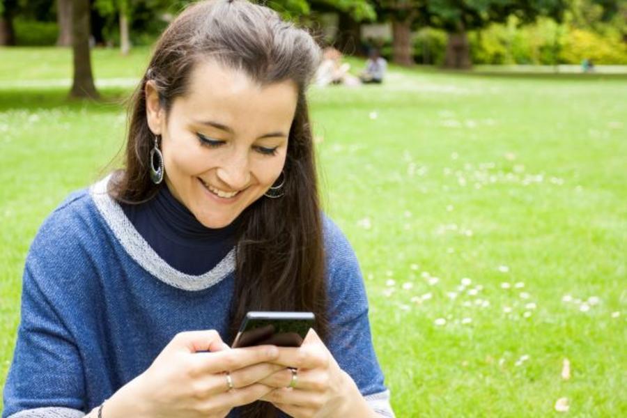 Ung kvinde der læser en ebog på sin telefon