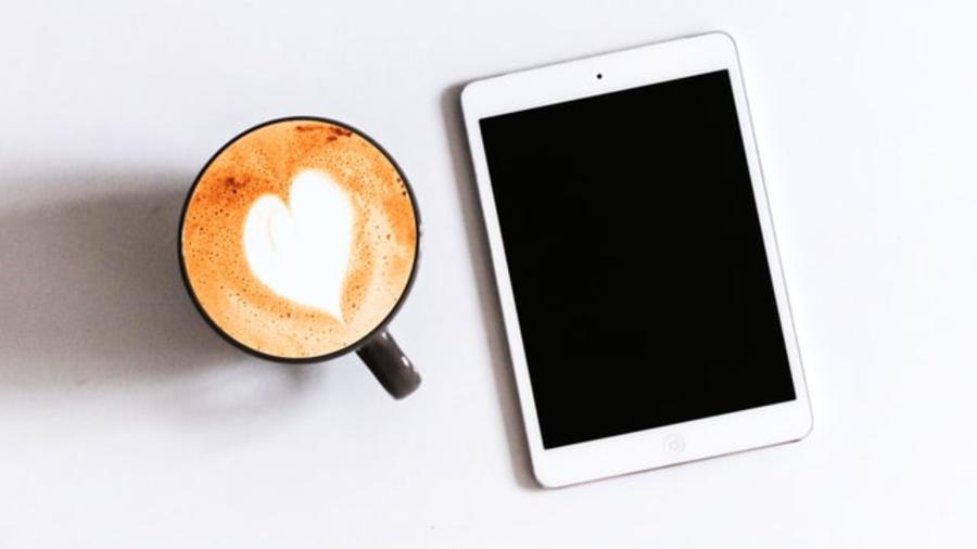 Tablet og en kop kaffe