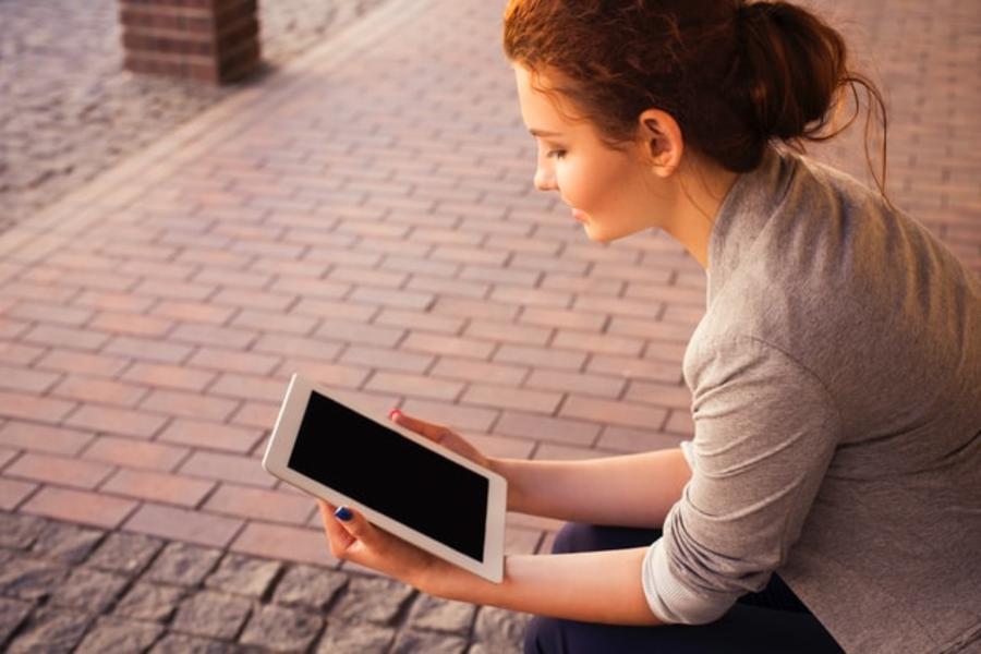 Ung kvinde læser en ebog på en bænk