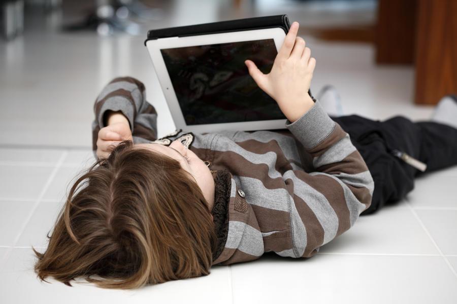 Dreng der ligger på gulvet og læser en ebog