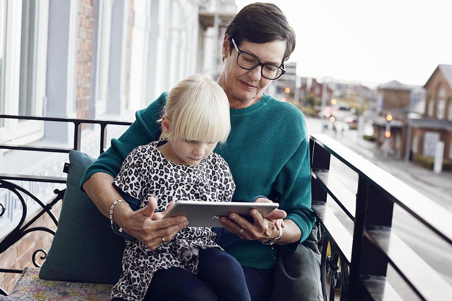 En pige og en kvinde læser en ebog sammen