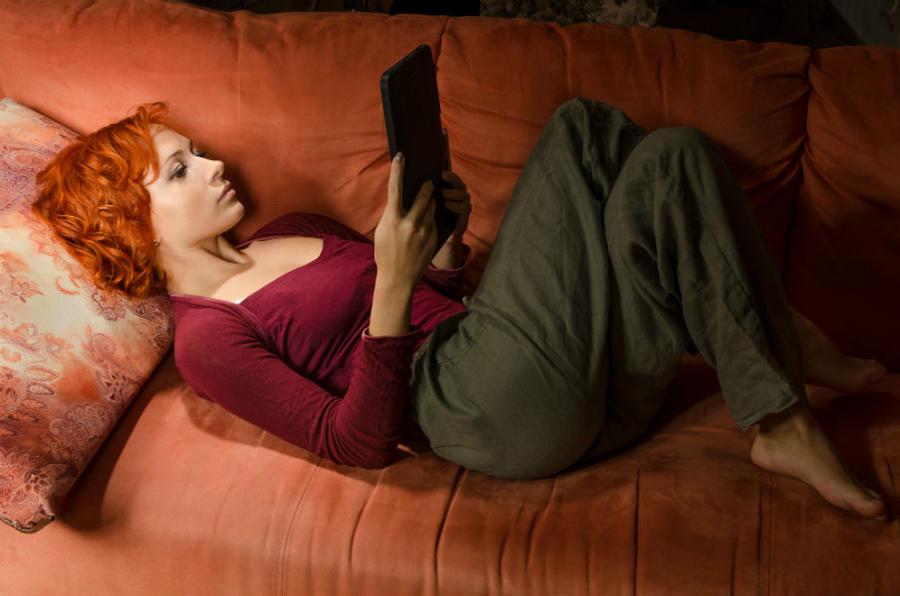 Kvinde ligger og læser en ebog