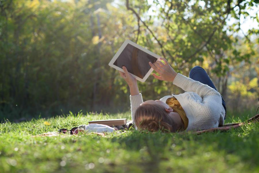 Kvinde ligger i græsset og læser en ebog