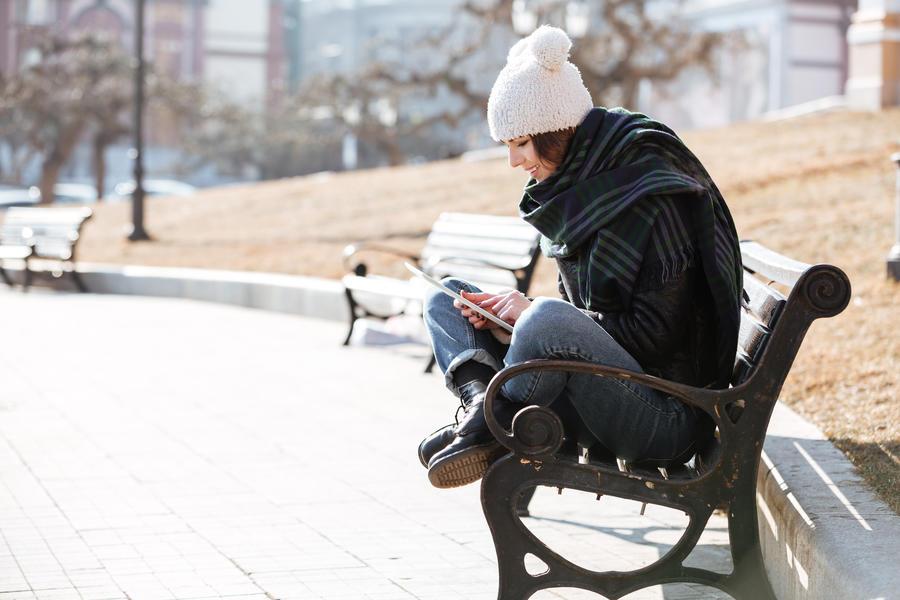 Kvinde sidder på en bænk og læser en ebog