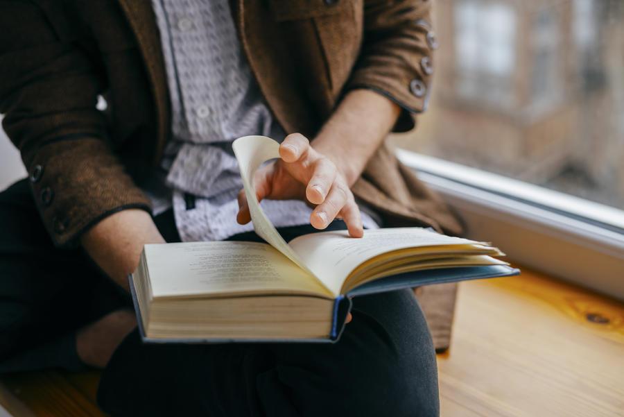 En bog i hænderne på en person