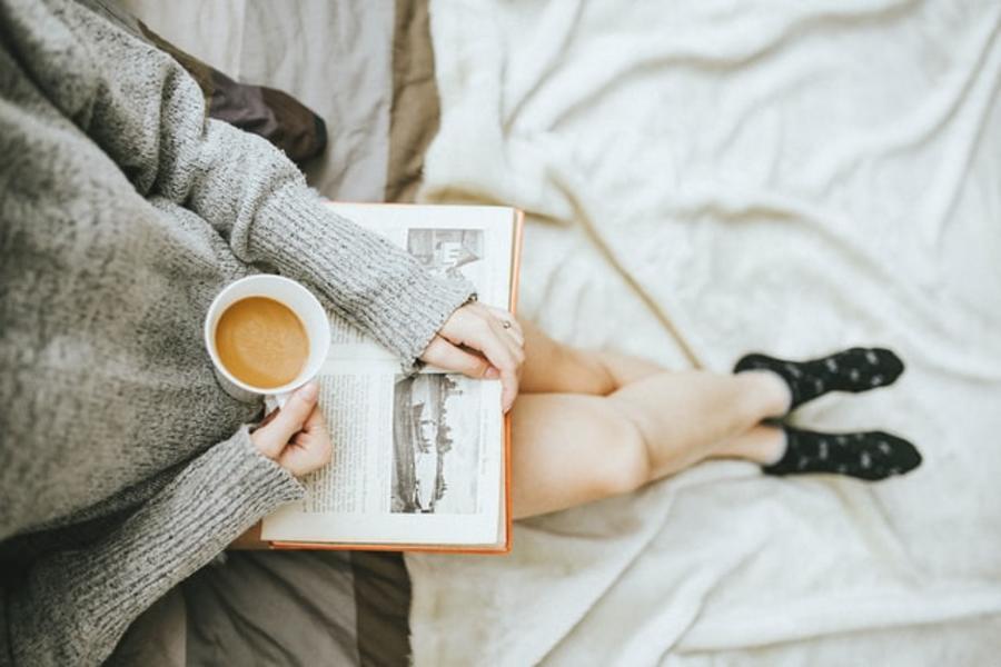 Kvinde læser i en bog og har en kop kaffe i hånden