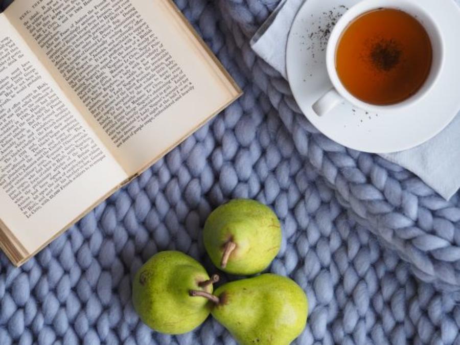 En bog og en kop te på et strikket tæppe