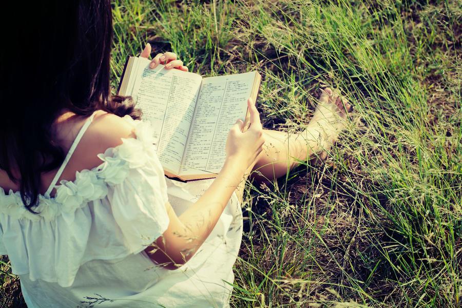 Ung kvinde læser under et træ
