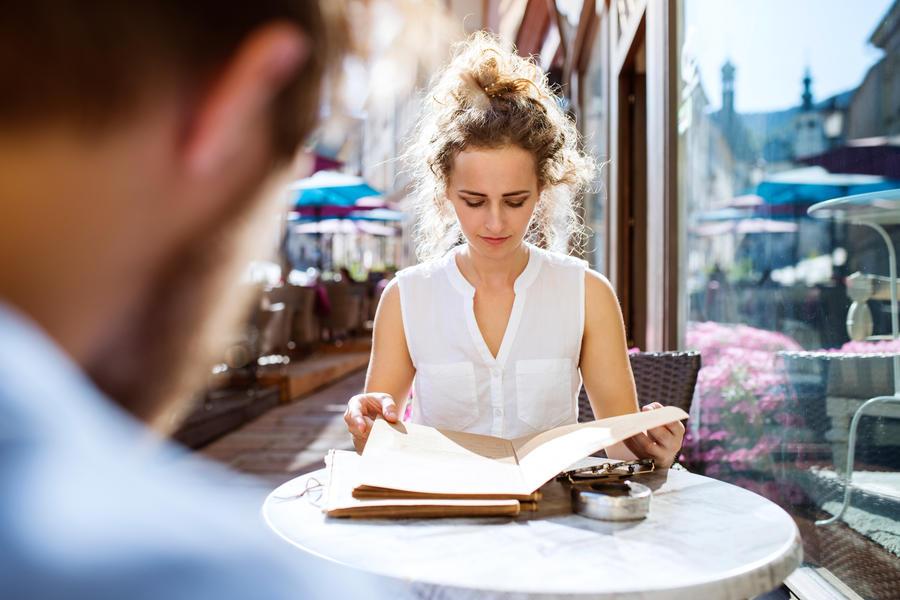 Kvinde sidder i solen og læser