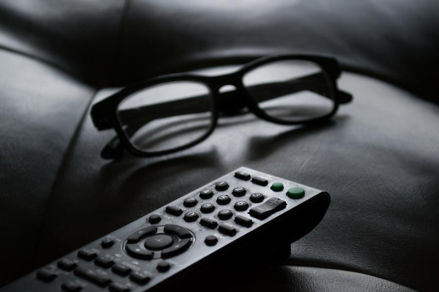Fjernbetjening og briller på et bord