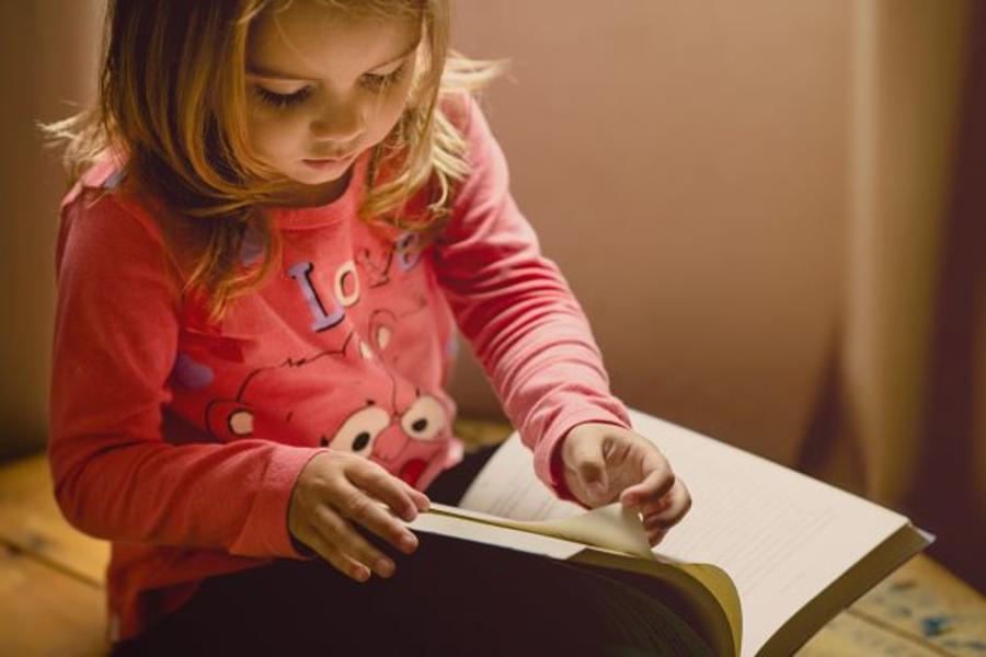 Pige der bladrer i en bog