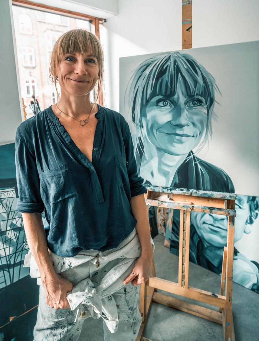 Kunstner Lise Eiler foran et malet selvportræt