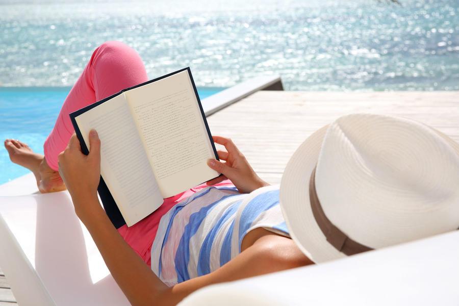 Kvinde ligger og læser i en liggestol ved en pool