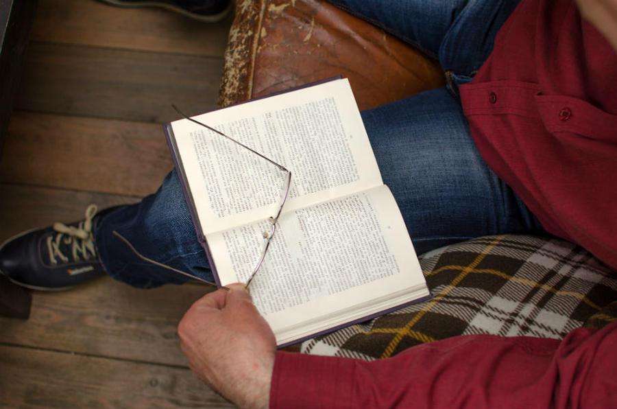 En opslået bog på et knæ