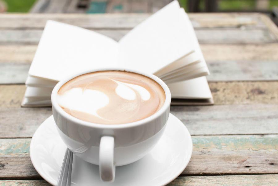 En kop kaffe og en bog på et bord