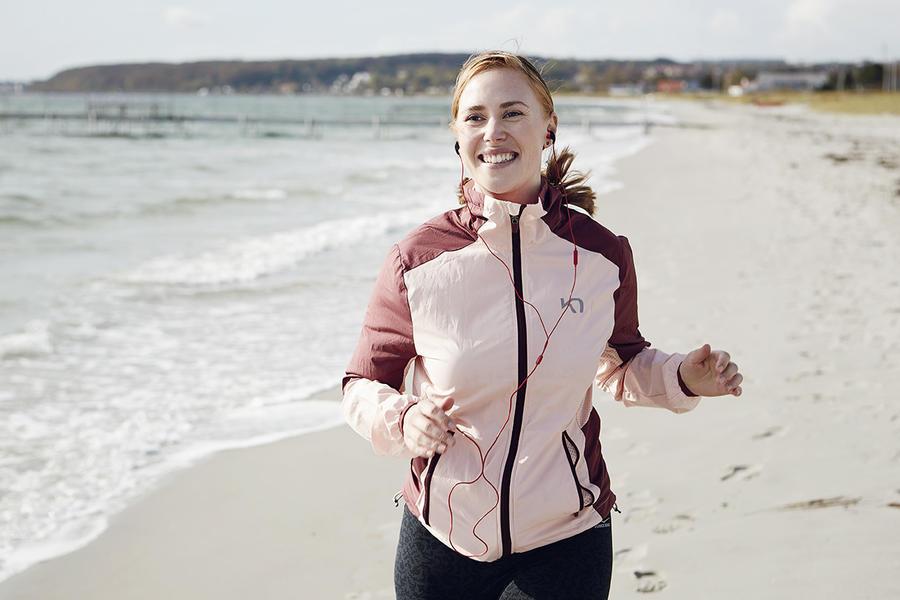 Kvinde løber på en strand og lytter til en lydbog