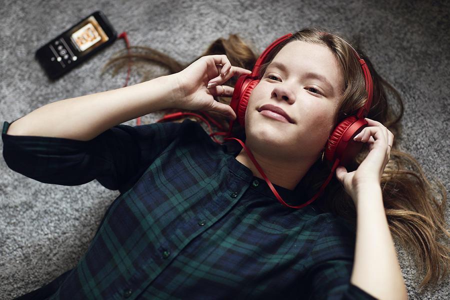 Pige ligger og lytter til en lydbog