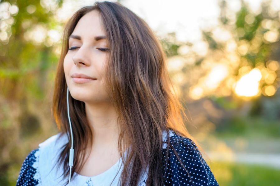Kvinde lytter til en lydbog i skoven