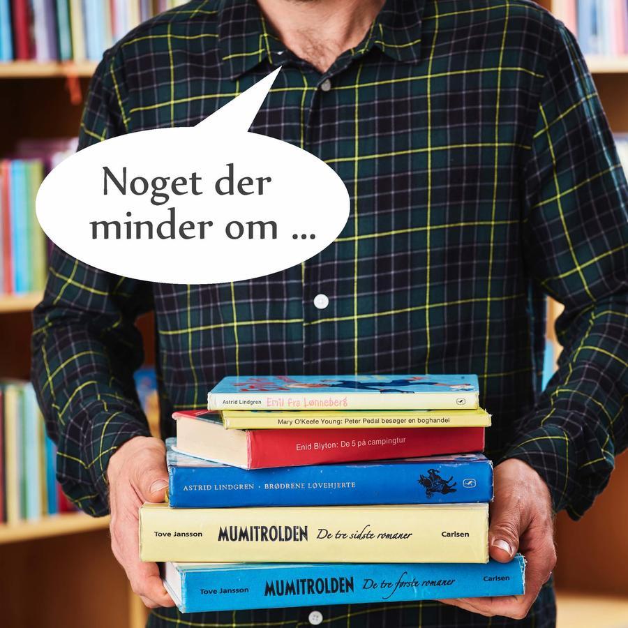 Billede af en mande, der har samlet en stak bøger