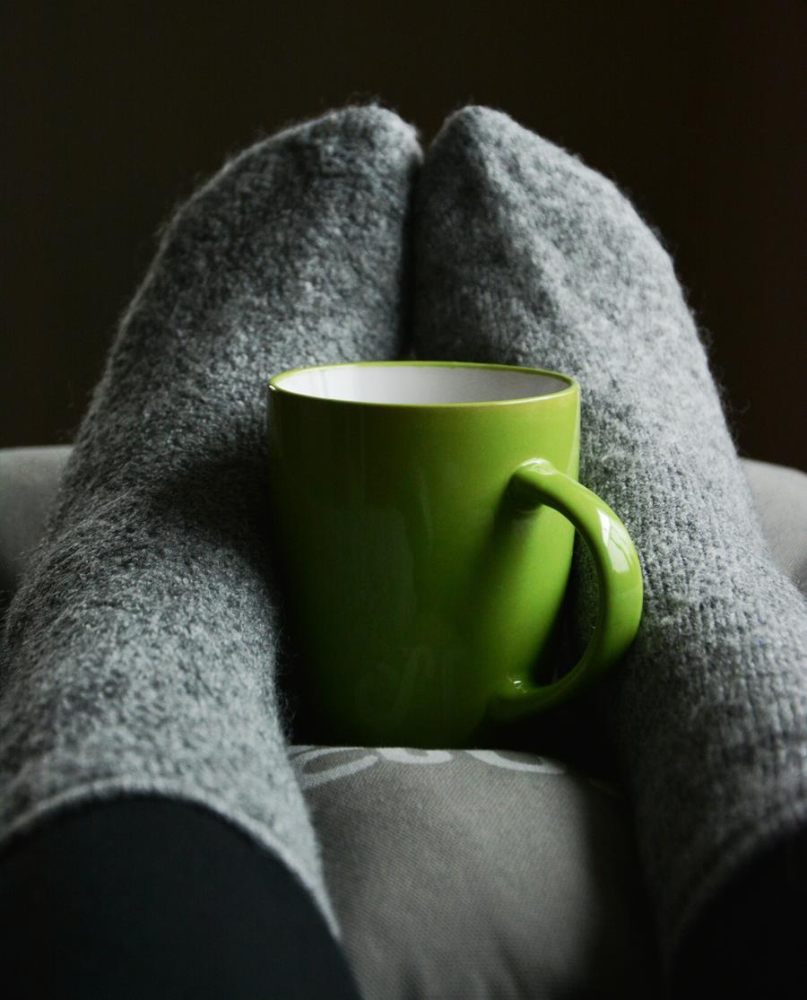 Grønt krus mellem fødder med varme sokker på
