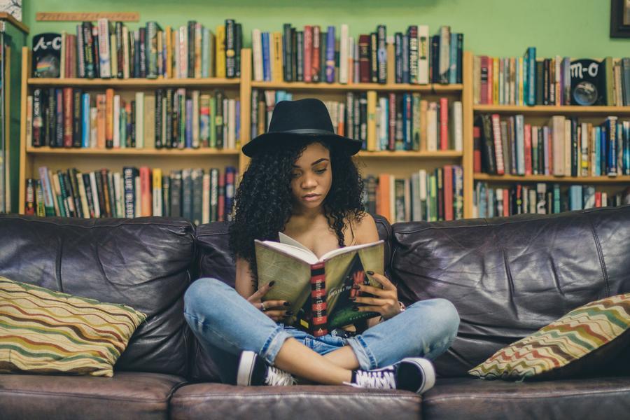 Ung pige sidder i en sofa og læser en bog