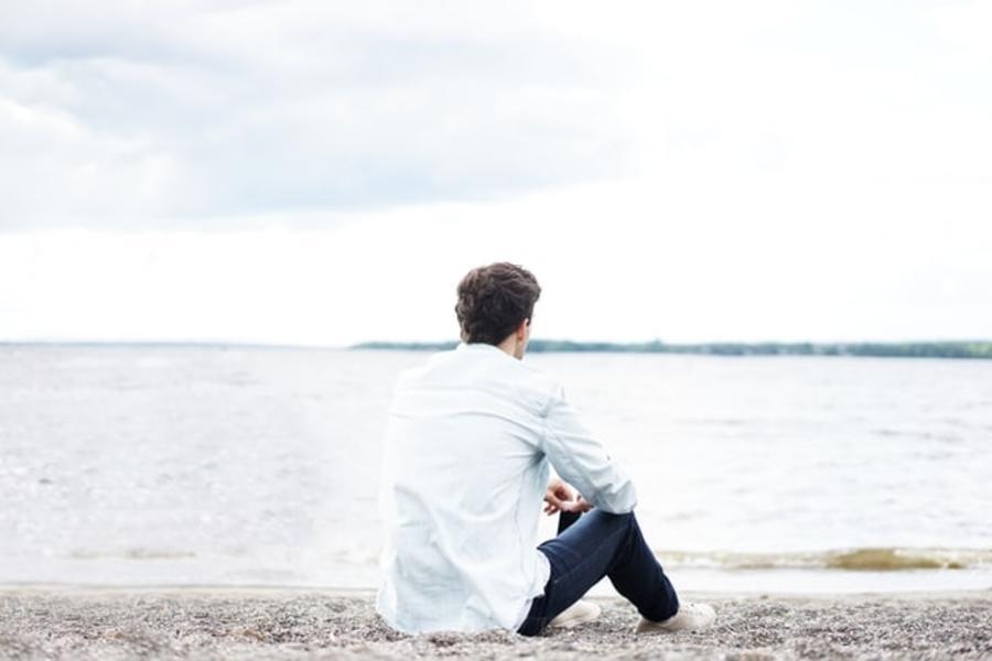 Mand sidder på en strand og ser ud over vandet