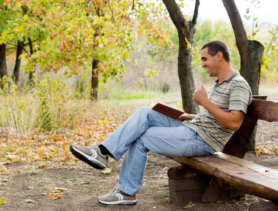 En mand sidder på en bænk i skoven og læser